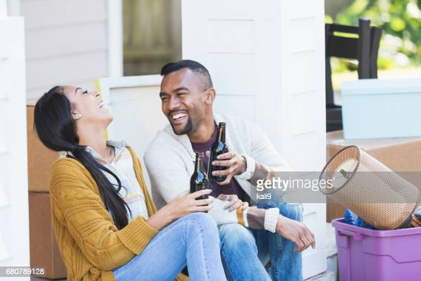 Young couple moving house, sitting on porch step