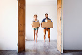 Young married couple moving in new house, holding big cardboard boxes.