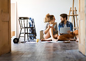 Young married couple with tablet moving in a new house, resting and making plans.