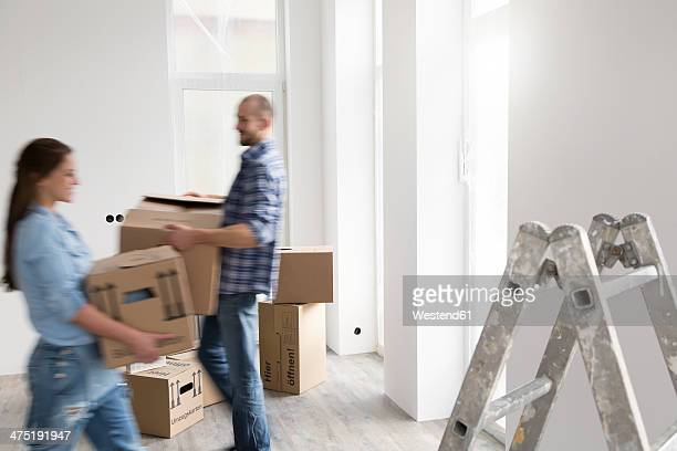 Young couple moving into new home, carrying cardboard boxes