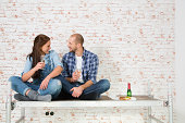 Young couple moving into new home, drinking champagne