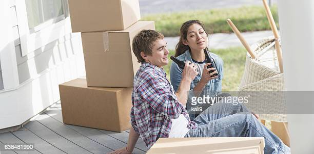 Young couple moving, taking a break, drinking