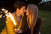 Young couple nose to nose in park holding sparkling firework