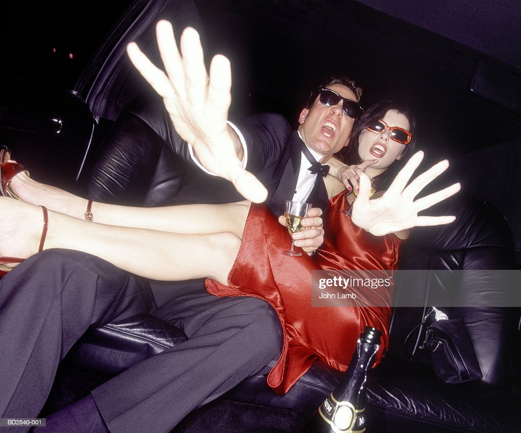 Young couple on back seat of limousine, hands in front of camera