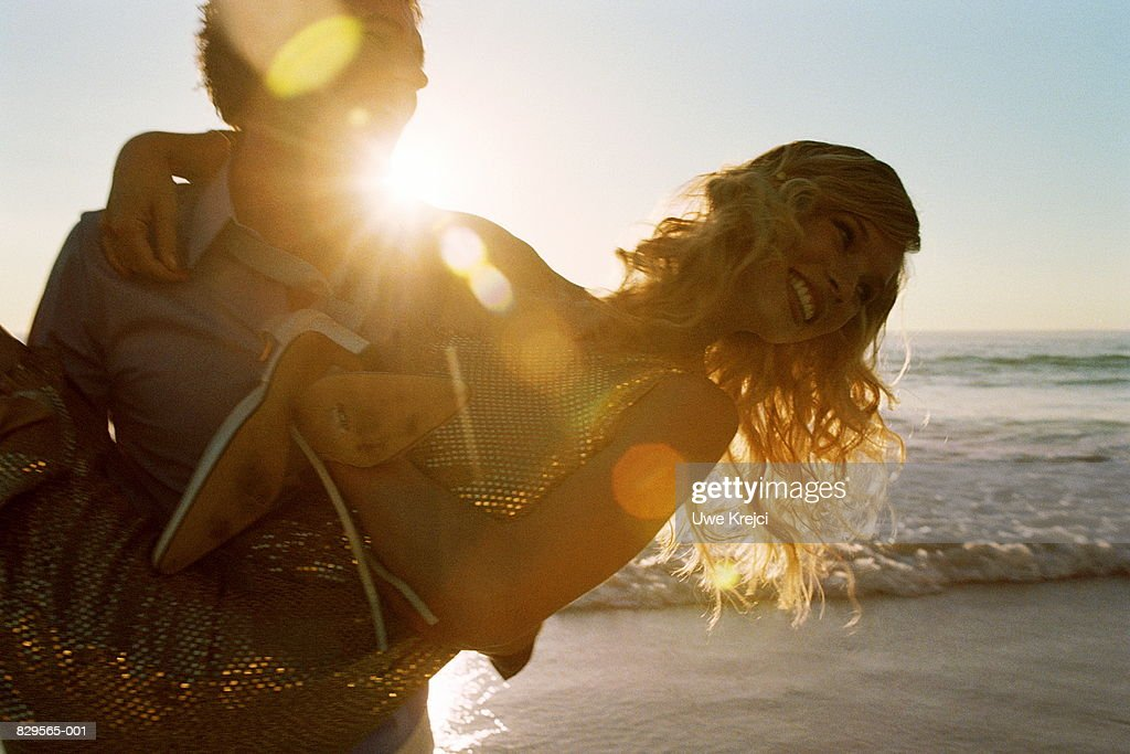 Young couple on beach at sunset, man carrying woman in arms : Stock Photo