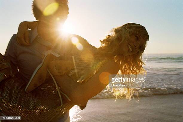 Young couple on beach at sunset, man carrying woman in arms