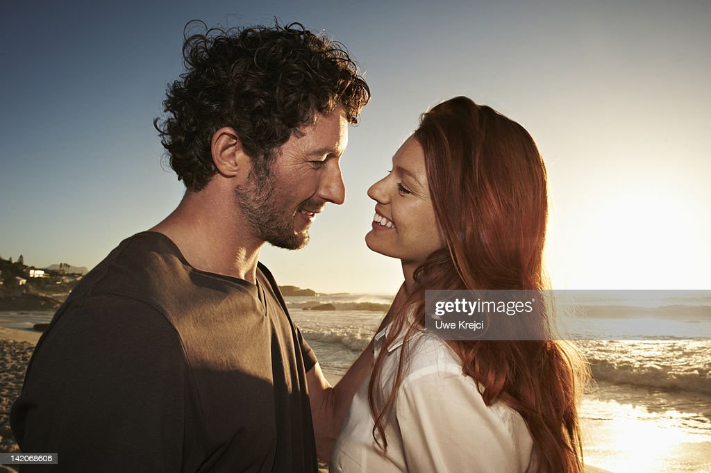 Young couple on beach at sunset : Stock Photo