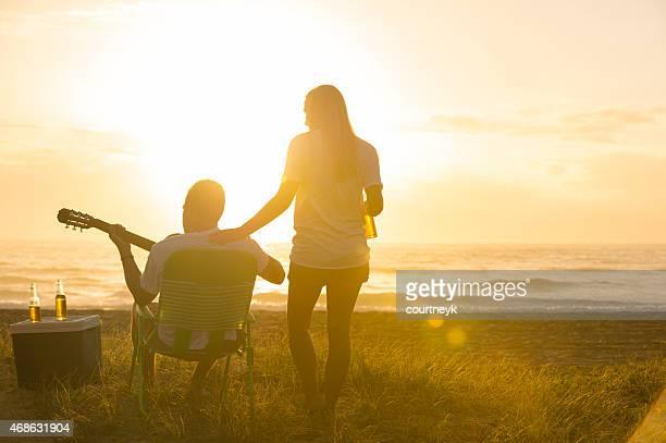 Giovane Coppia sulla spiaggia guardando al tramonto con chitarra.