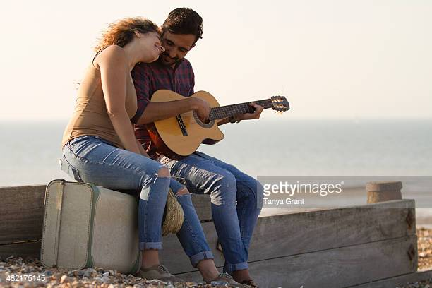 Young couple on beach, man playing guitar