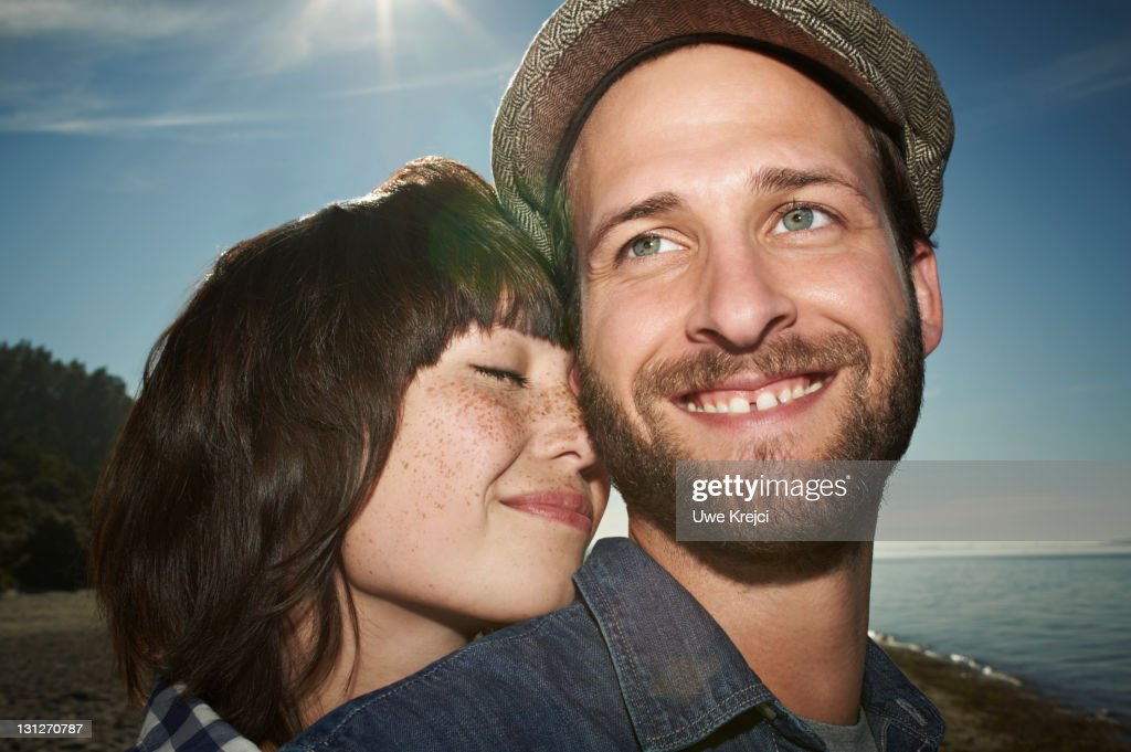 Young couple on beach, smiling, close up : Stock Photo