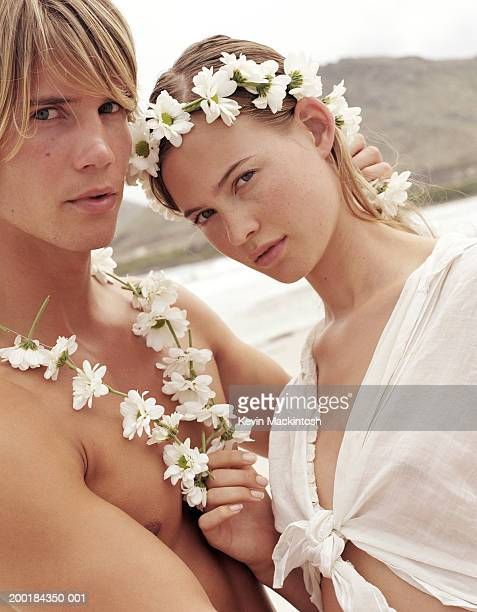 Young couple on beach wearing flower garlands, portrait, close-up