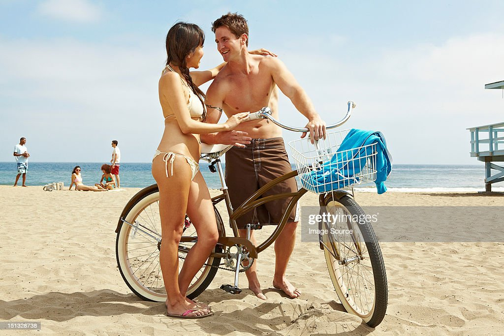 Young couple on beach with bicycle