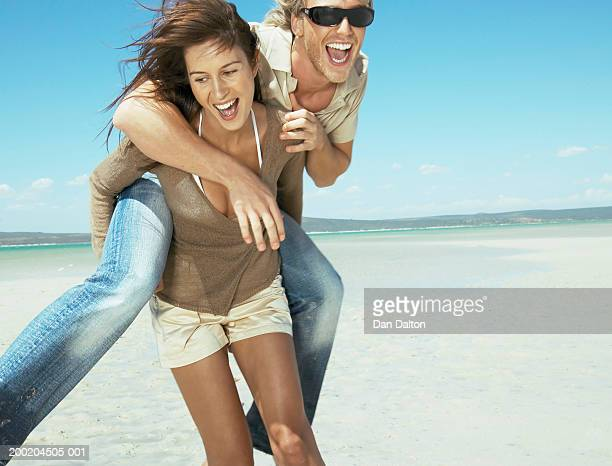 Young couple on beach, woman giving man piggy back, laughing