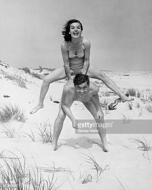 Young couple on beach, woman leap-frogging man, (B&W), portrait