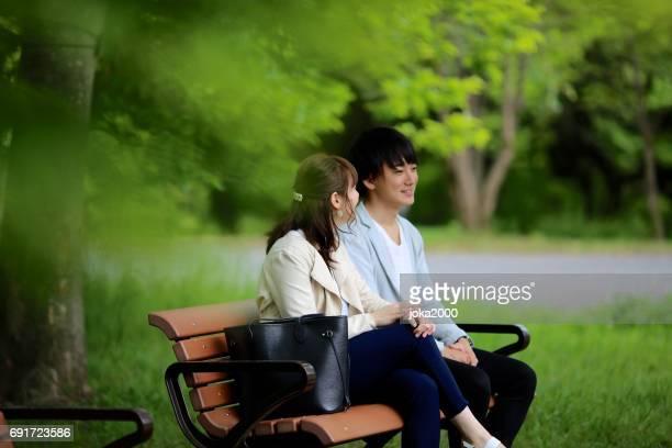 ベンチの公園で春を楽しむ若いカップルします。