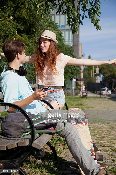 Young couple on bench listening to music
