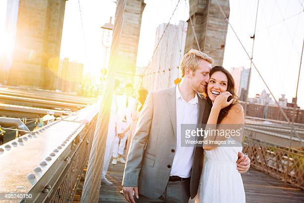 Young couple on Brooklyn Bridge at sunset