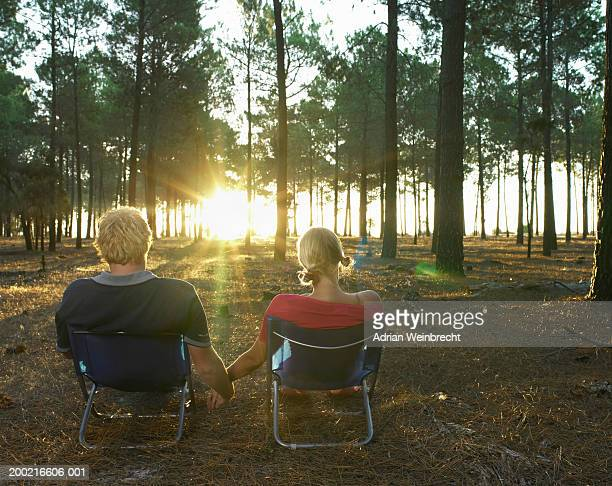 Young couple on camping chairs in wood, watching sunrise, rear view