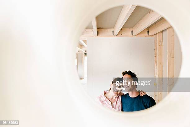 young couple on construction site of their new home seen through hole in wall