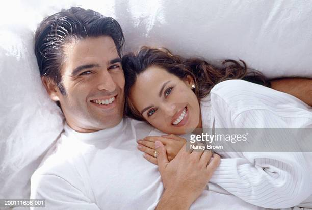 Young couple on couch smiling, close-up, portrait