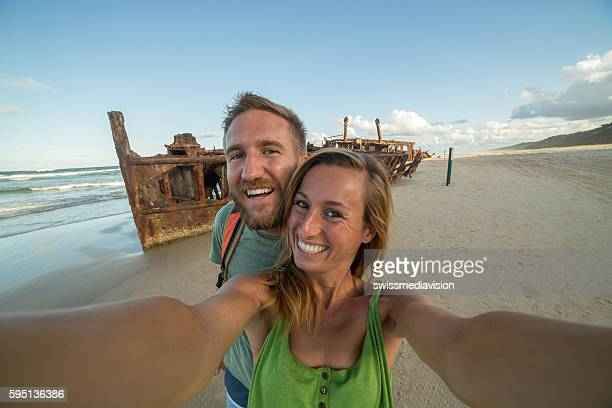 Young couple on Fraser Island take selfie with shipwreck