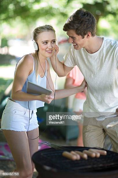 Young couple on holiday grilling sausages and listening to music on a digital tablet