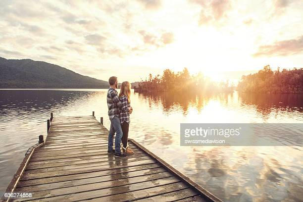 Young couple on lake pier sharing special moment