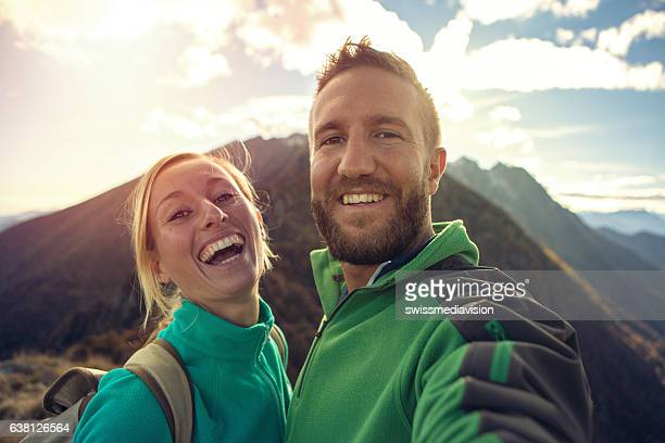 Young couple on mountain top take selfie portrait