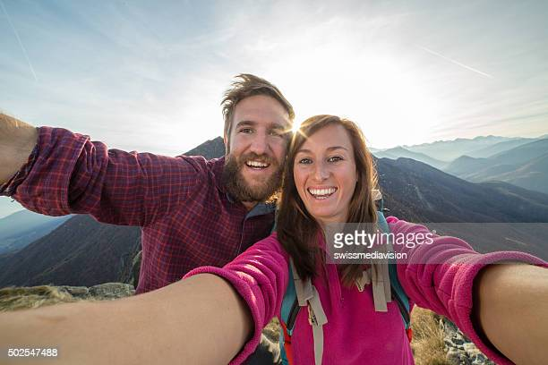 Young couple on mountain top takes selfie portrait