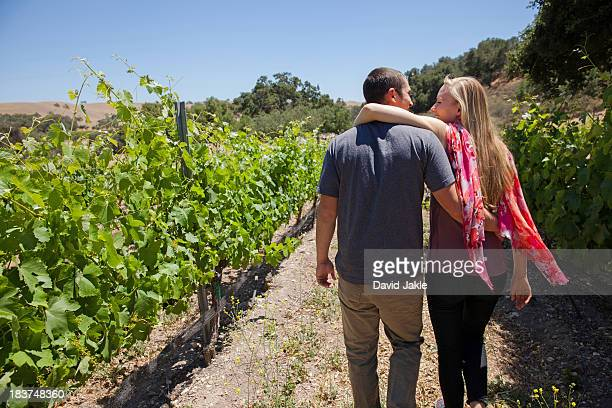 Young couple on path in vineyard, woman with arm around man