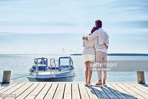Young couple on pier looking at view, Gavle, Sweden
