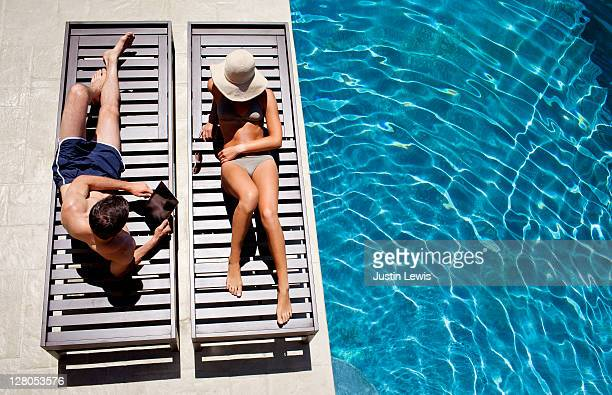 young couple on pool chairs next to luxury pool