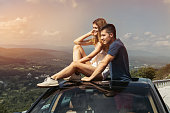 Young couple on road trip travel by car together and enjoy the nature view from the top