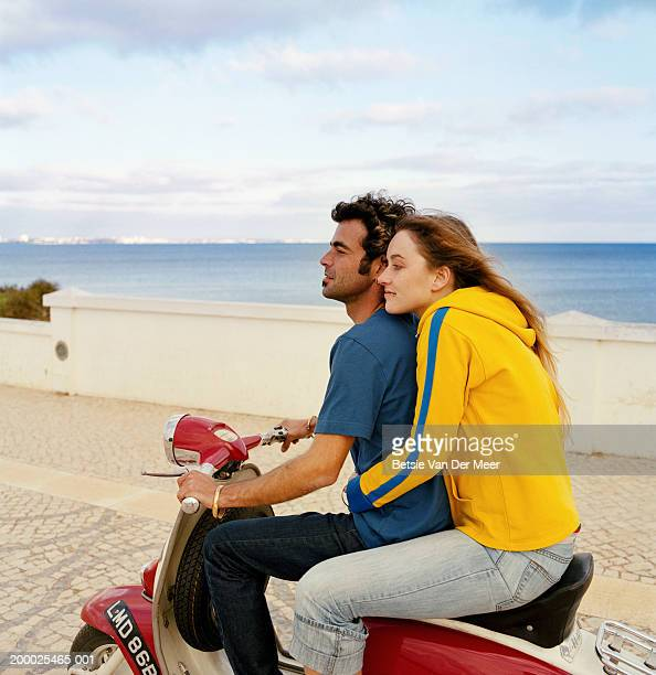 Young couple on scooter by sea
