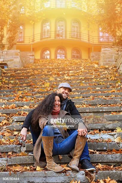 Jeune couple sur les escaliers dans à l'avant de jaune ensoleillé maison