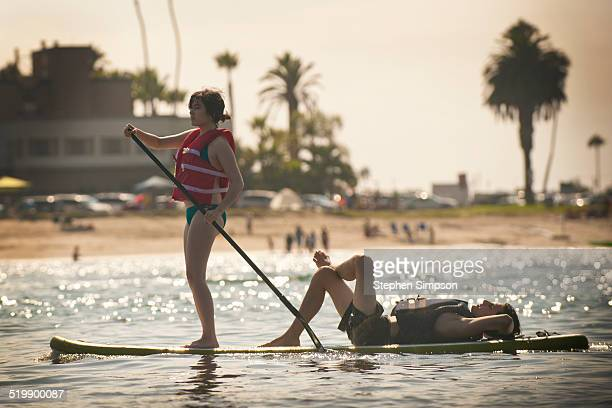 young couple on stand-up paddle board