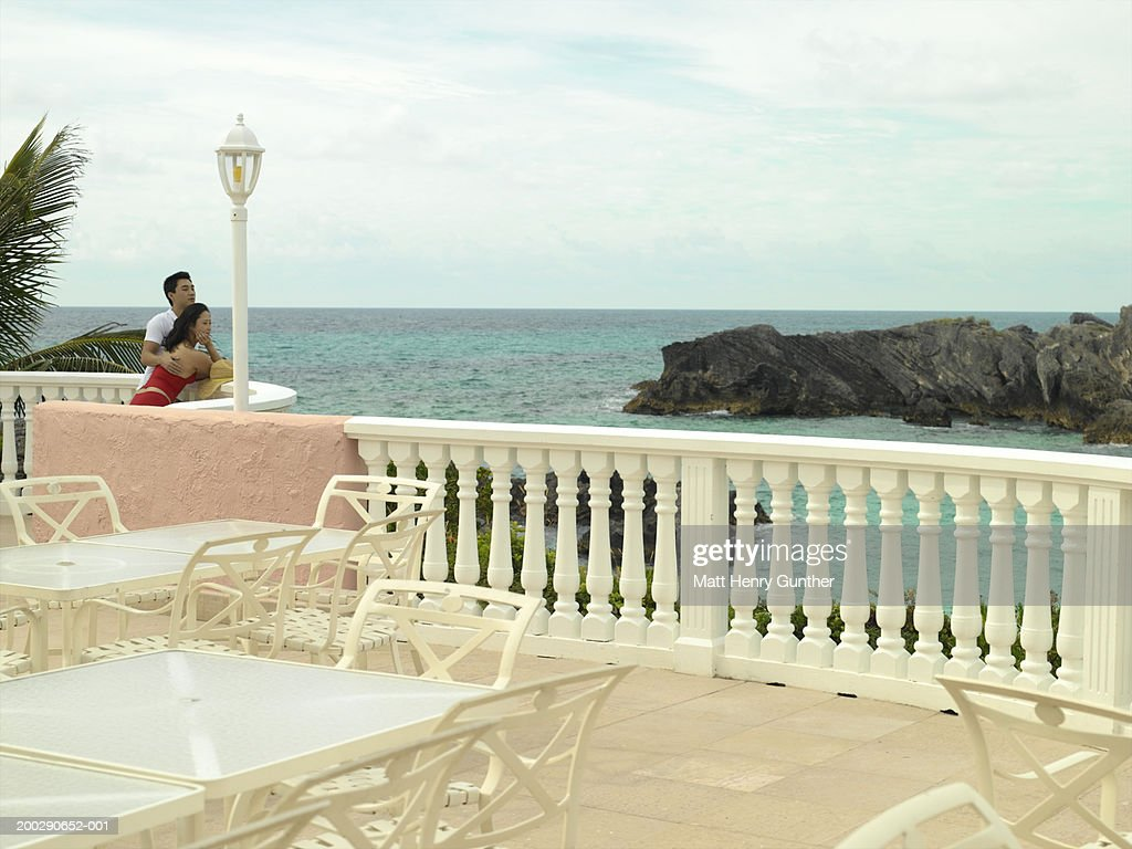 Young couple on terrace overlooking sea : Stock Photo