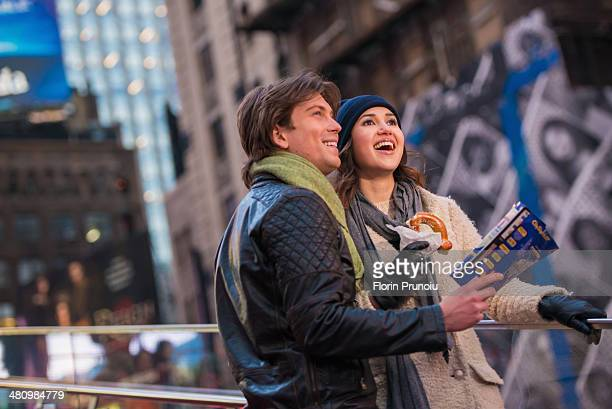 Young couple on vacation with map and bagel, New York City, USA