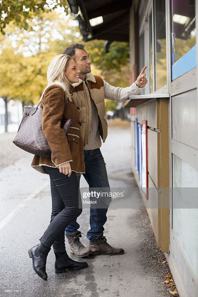 Young couple ordering food from store on street