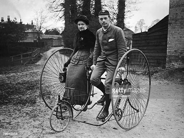 A young couple out cycling in Putney on a tandem penny farthing tricycle circa 1890
