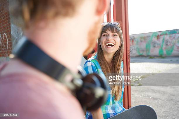 Young couple outdoors, face to face, young woman laughing