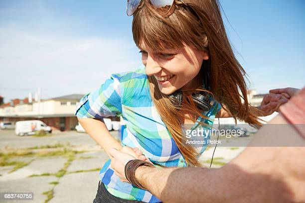 Young couple outdoors, holding hands, fooling around