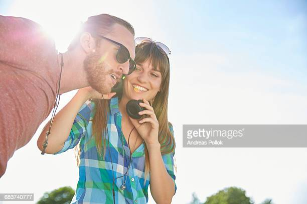 Young couple outdoors, listening to music through headphones