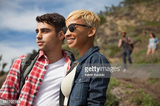 Young couple, outdoors, looking at view, friends trailing behind