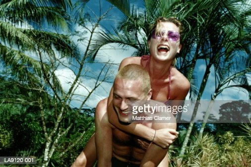 Young couple outdoors, man giving woman piggyback ride : Stock Photo
