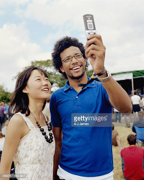 Young couple outdoors, man taking photo with mobile phone
