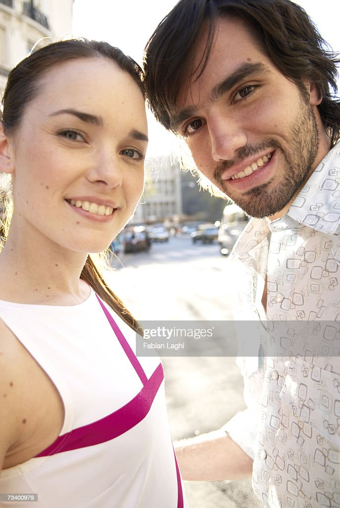 Young couple outdoors, smiling, portrait : Stock Photo