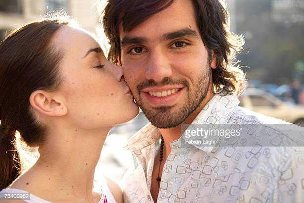 Young couple outdoors, woman kissing man's cheek, portrait