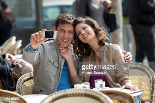 A young couple outside a Paris cafe : Stock Photo