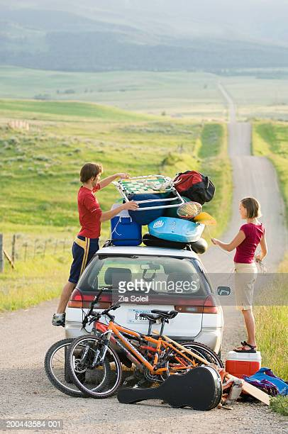Young couple packing car with vacation gear on empty road